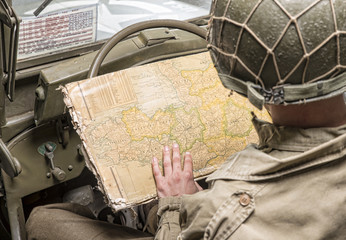 driver of a military vehicle look at a map of Normandy