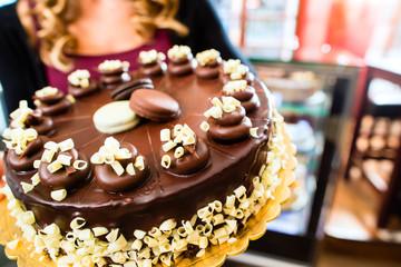 Bäckerin präsentiert Torte in Patisserie