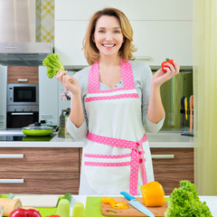 Happy young woman cooking a salad.