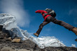 Hiker jumps over rocks in Himalaya mountains