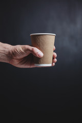 Man's hand holding a paper cup