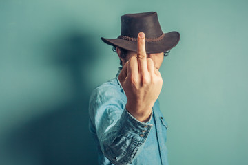 Cowboy displaying obscene gesture
