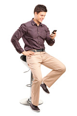 Fashionable man texting by a mobile phone