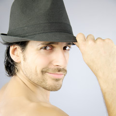 Happy man with cool hat smiling in studio