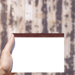 white blank notebook in hand and wooden background