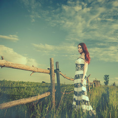 young redhead woman at old meadow fence