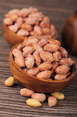 Salted roasted peanuts in wooden bowl