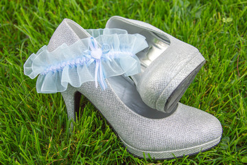 Light blue lace garter arranged with silver high heel shoes
