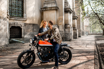 Girl running to her boyfriend sitting on the motorcycle