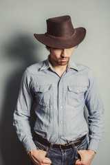 Cowboy standing by a blue wall