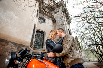 Couple embracing near the motorcycle on the old city