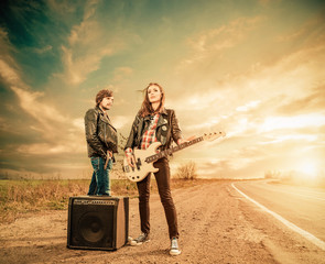 young stylish musicians on a road to horizon