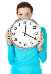 Happy woman holding office clock