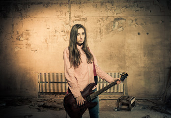 young artistic woman with guitar at old dark room