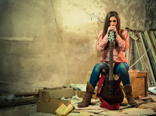 young woman in shirt and jeans with guitar at old abandoned room