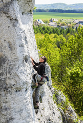 Man climbing natural rocky wall.