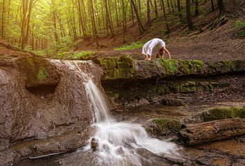 Woman practices yoga in nature, the waterfall.