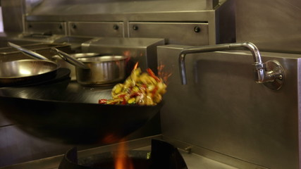 Chef tossing vegetables in a wok over a large flame