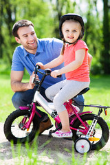 Little girl learning to ride a bike with her father