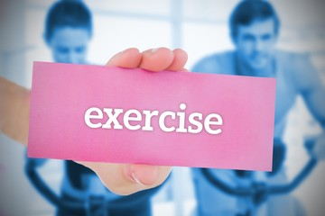 Woman holding pink card saying exercise