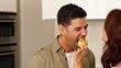 Woman feeding her boyfriend a green apple jokingly