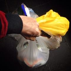 Hand trägt Müllbeutel