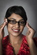 Young Indian woman with framed glasses, smiling