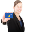 business woman holding a card with the flag of Kosovo