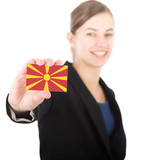 business woman holding a card with the flag of Macedonia