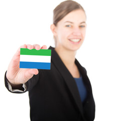 business woman holding a card with the flag of Sierra Leone