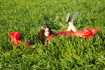 young lady in red dress lie on field