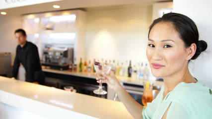 Asian woman smiling at camera drinking a cocktail