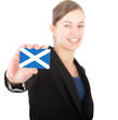 business woman holding a card with the flag of Scotland