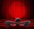 man sitting alone in  empty theater or cinema hall - 64760804