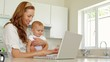 Beautiful brunette using laptop and holding her baby daughter