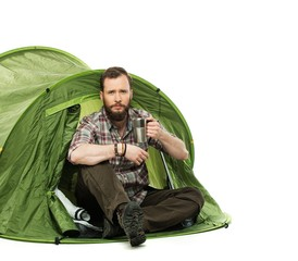 Handsome traveler in a tent with coffee cup