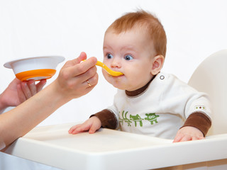 Little baby eats puree from the spoon