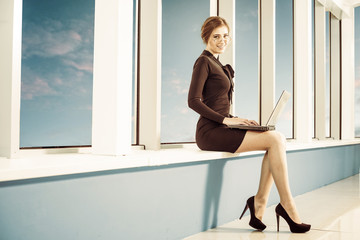 lady with laptop at office windowsill