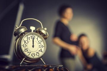 Pregnant women and alarm clock. Selective focus on clock.