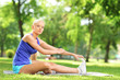 Athlete woman sitting on an excercising mat and stretching