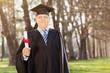 Mature college graduate holding diploma in park