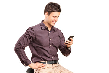 Fashionable man texting by a cell phone