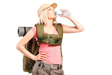 Female hiker with backpack drinking water