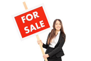 Female real estate agent holding a for sale sign