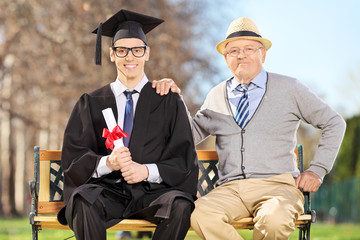 Male graduate posing with his father