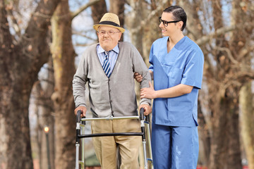 Medical professional helping a senior with walker in park