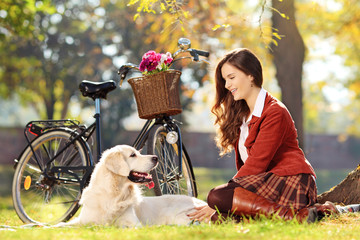 Pretty female sitting down with her dog in park