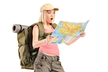 Surprised female hiker looking at a map