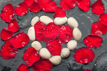 The symbolic heart of the white stones among red rose petals