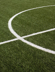 Part of a soccer field with green synthetic grass closeup